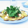 Op het bord gebakken aardappelen met rucola salade